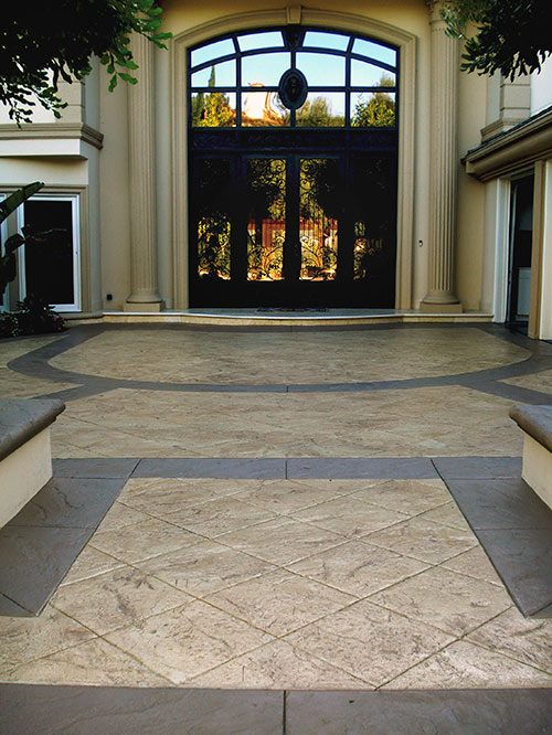 Huge entry near front gate of an indoor garden area with stamped colored concrete