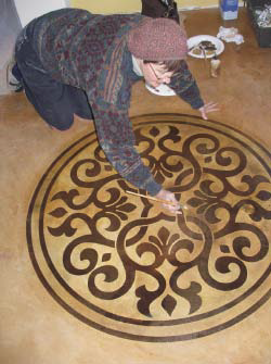 Gaye Goodman gets down to it installing a stencil onto an acid stained floor