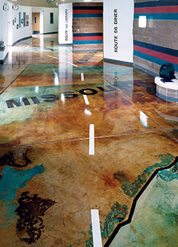 The use of a high gloss sealer over a stained concrete floor that has been designed after a large scale map.