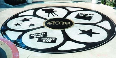 Stencil application with sandblasting created this theater black and white logo on the floor to the entrance.