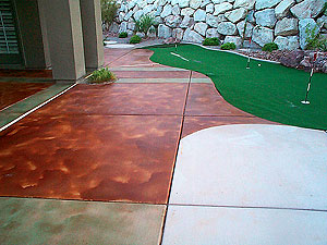 A putting green surrounded by an acid stained patio by Floor Seasons.
