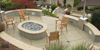 Upper patio of a backyard made with concrete and a firepit