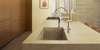 A look at a big basin of a sink built into concrete countertops.